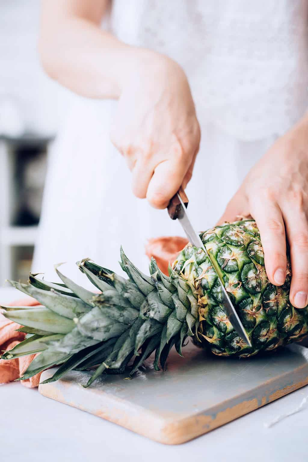 Cutting top off of a pineapple